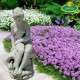 Kerti szobor nő sziklán üllő korsós vízköpő